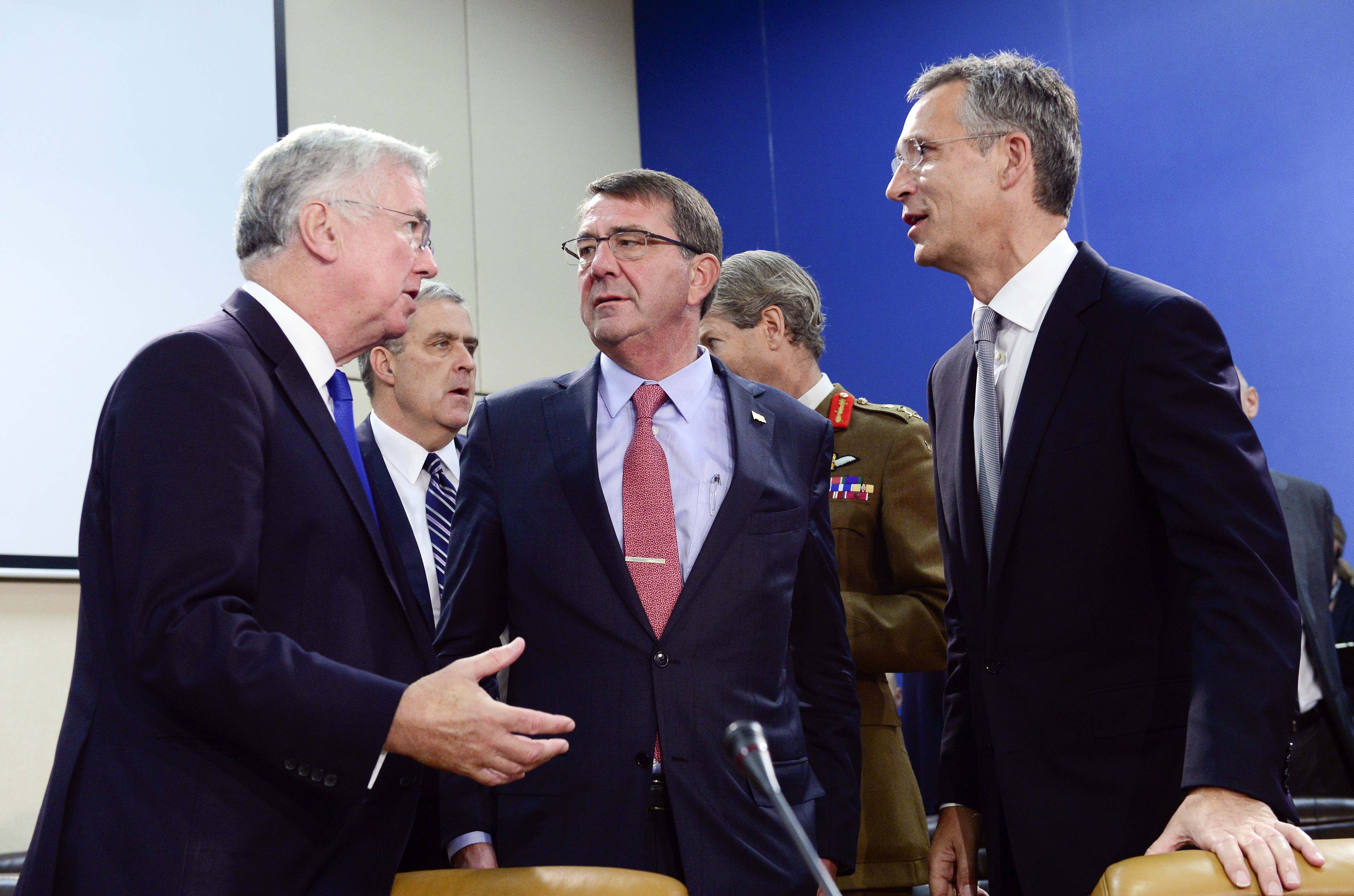 UK Defence Secretary Michael Fallon (left), U.S. Defense Secretary Ash Carter (center), and NATO Secretary-General Jens Stoltenberg confer during a meeting of defense ministers at NATO headquarters in Brussels on October 8. [Photo credit: John Thys /AFP/Getty Images]