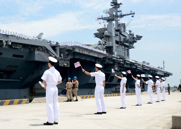 South Korean sailors wave South Korean and U.S. flags as the aircraft carrier USS George Washington arrives in Busan for a port visit on July 11, 2014. (Photo credit: Mass Comm. Spec. 1st Class Frank L. Andrews/U.S. Navy)