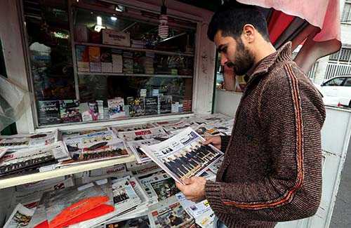 A man looks at newspapers displayed outside a kiosk in Tehran on November 25, a day after Iran and the P5+1 announced that they were extending their talks for a second time. (ATTA KENARE/AFP/Getty Images)