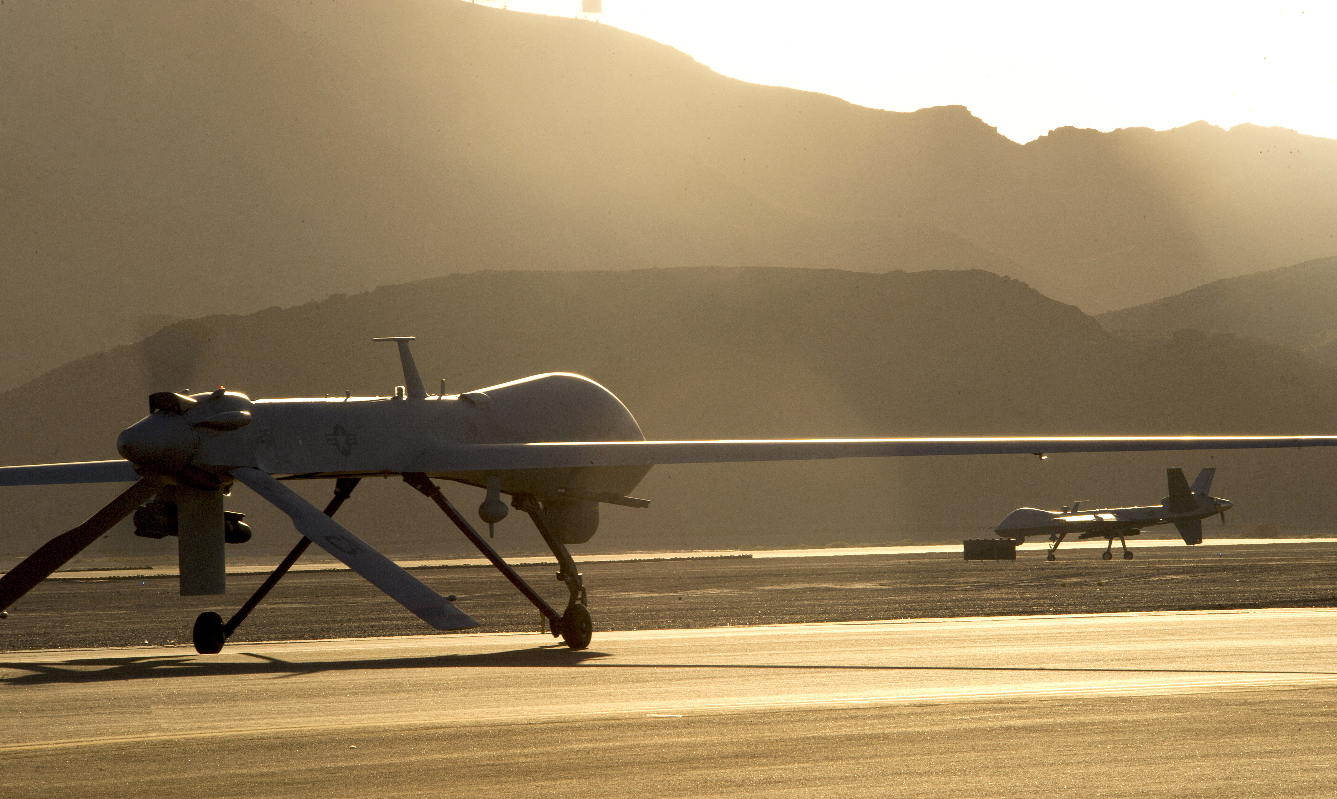 An MQ-1B Predator drone (left) and an MQ-9 Reaper drone taxi to the runway in preparation for takeoff from Creech Air Force Base in Nevada on June 13, 2014. (Airman 1st Class Christian Clausen/U.S. Air Force)