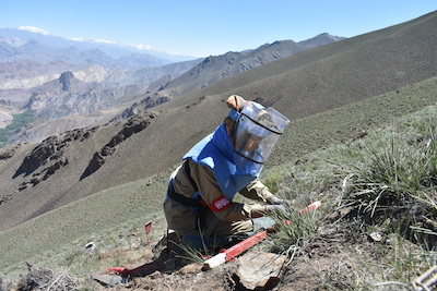 A member of Afghanistan's all-woman demining team clearing a mine in Bamyan province.