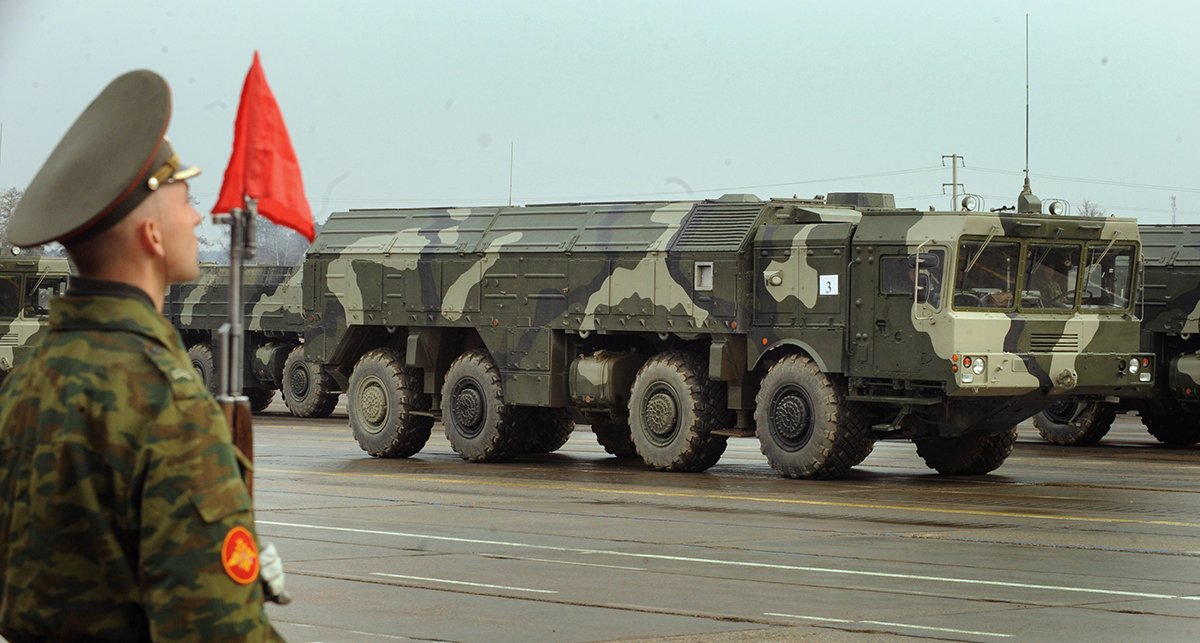 A Russian Iskander ballistic missile launcher rolls by a soldier during a parade rehearsal near Moscow on April 20, 2010. Recently, Russia reportedly has deployed Iskander-M missiles, which can carry conventional or nuclear warheads, to its western enclave of Kaliningrad, which borders NATO members Poland and Lithuania. (Photo credit: Alexander Nemenov/AFP/Getty Images)