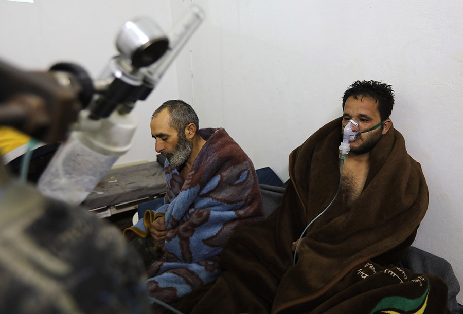 Syrians reportedly suffering from breathing difficulties following Syrian regime's Feb. 4 air strikes on the northwestern town of Saraqeb rest around a stove at a field hospital. (Photo: Omar Haj Kadour/AFP/Getty Images)