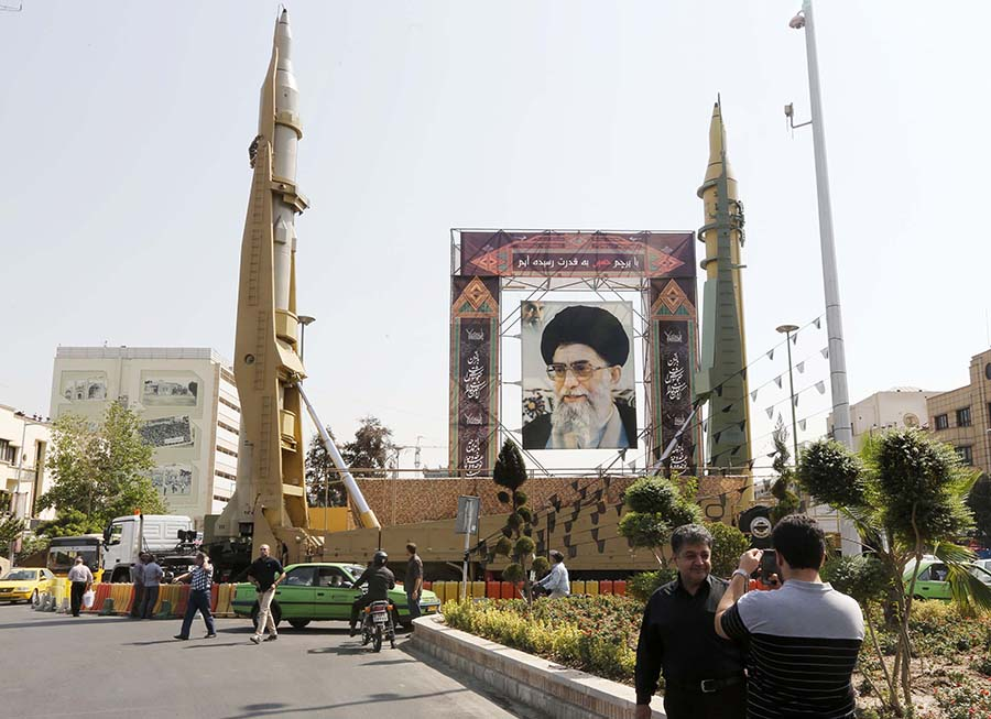 Iranian Sejjil (left) and Ghadr-H medium-range ballistic missiles are displayed in Tehran September 25, 2017 next to a portrait of Supreme Leader Ayatollah Ali Khamenei during annual defense-week events. (Photo: Atta Kenare/AFP/Getty Images)