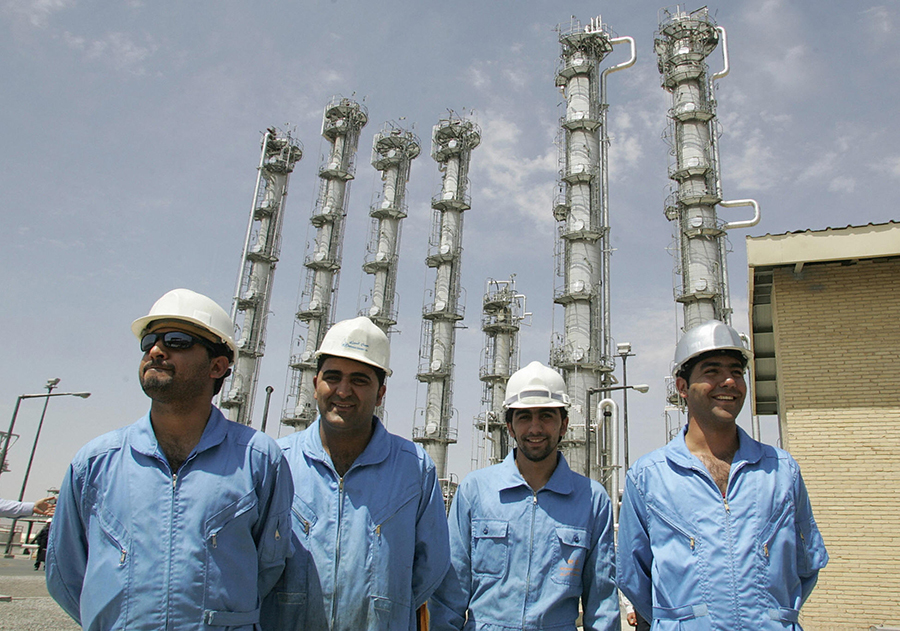 Iranian workers smile at the nation's newly opened heavy water production plant in Arak in 2006. Iran has moved closer to storing more heavy water than allowed by the 2015 nuclear deal. (Photo: Atta Kenare/AFP/Getty Images)